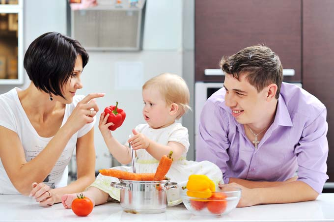 Attractive Couple with Baby examine different vegetables on Kitchen Counter
