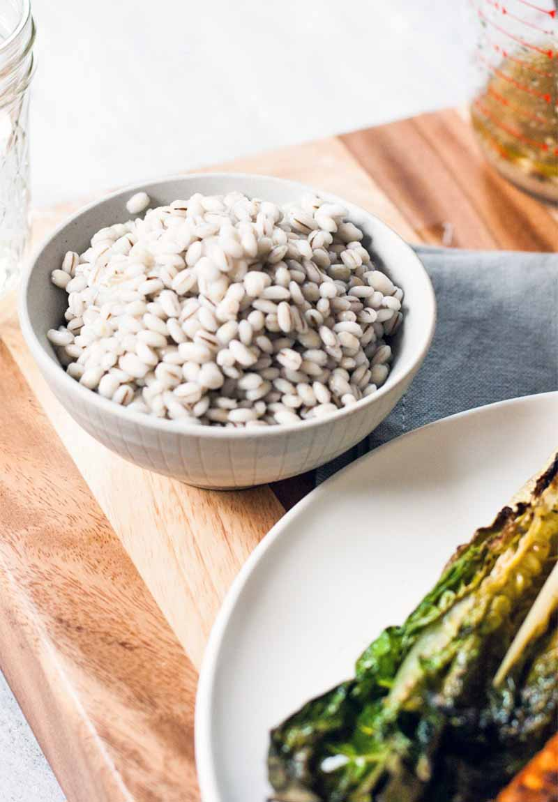 A small white bowl of cooked barley beside a plate of wilted grilled romaine lettuce, on a wood cutting board with a folded gray cloth.