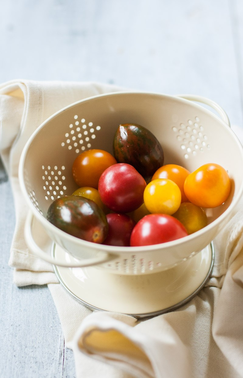A colander of red, purple, and yellow cherry tomatoes.