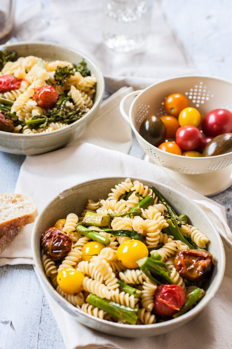 An oblique view of two white, porcelain bowls full of grilled tomato and broccolini pasta salad with balsamic vinaigrette on a white tablecloth.