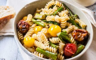 An oblique view of a single bowl full of Grilled Tomato and Broccoli Pasta Salad with Balsamic Vinaigrette.