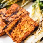 Closeup of three rectangular pieces of marinated and grilled tofu beside wilted and charred romaine lettuce, on a white plate.