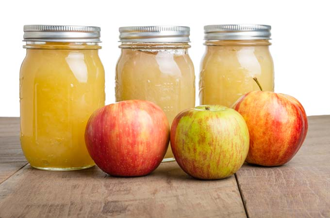 Three mason jars of Apple sauce behind three fresh apples on primative wooden table