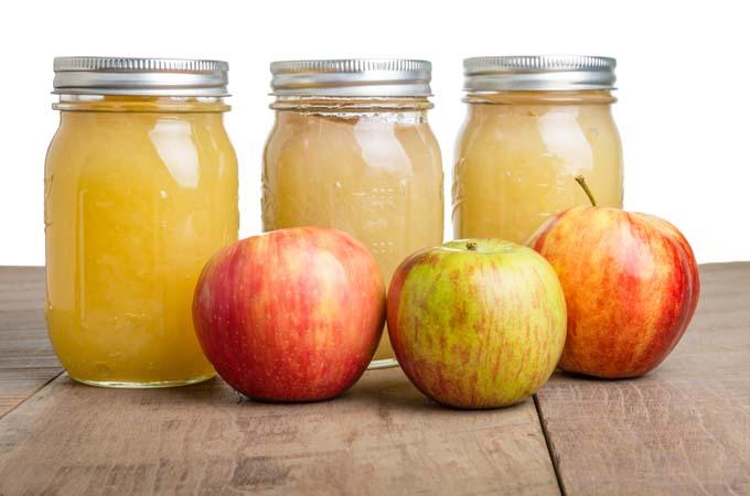 Three mason jars of Apple sauce behind three fresh apples on primative ...