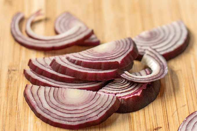 Closeup of sliced red onion on a brown wood background.