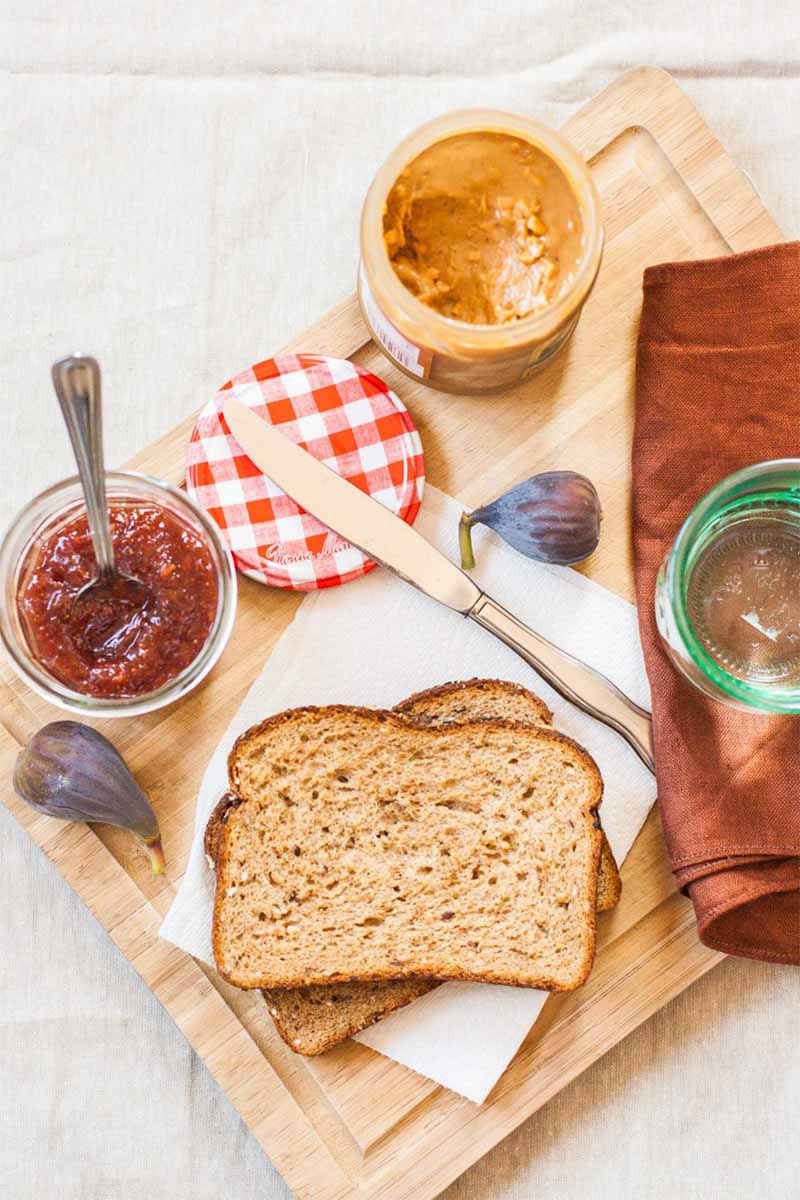 Vertical top-down image of two slices of whole wheat sandwich bread, two whole figs, a jar of fruit spread with a spoon in it, a knife, a red and white lid, a jar of peanut butter, a brown cloth napkin, and a green glass jar.
