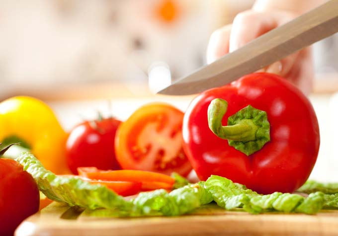 Female hand with slicing knife cutting up red bell pepper on cutting board