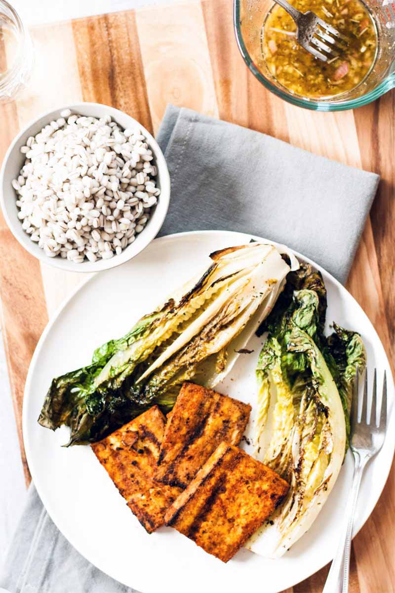 Top-down shot of orange paprika marinated tofu and wilted and charred romaine on a white plate with a fork, beside a small white bowl of cooked barley and a bowl of shallot dressing, on a wood cutting board with a folded gray cloth napkin.