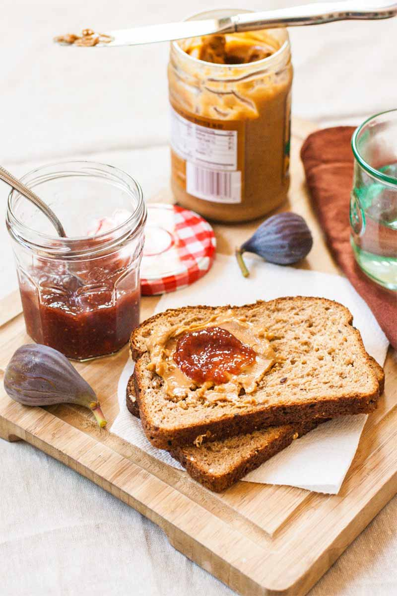Vertical image of two stacked pieces of whole wheat bread with a dollop of peanut butter and jelly on top, with a jar of fig jam, scattered whole fruit, a jar of spread, and a folded brown cloth napkin, on a wood cutting board.