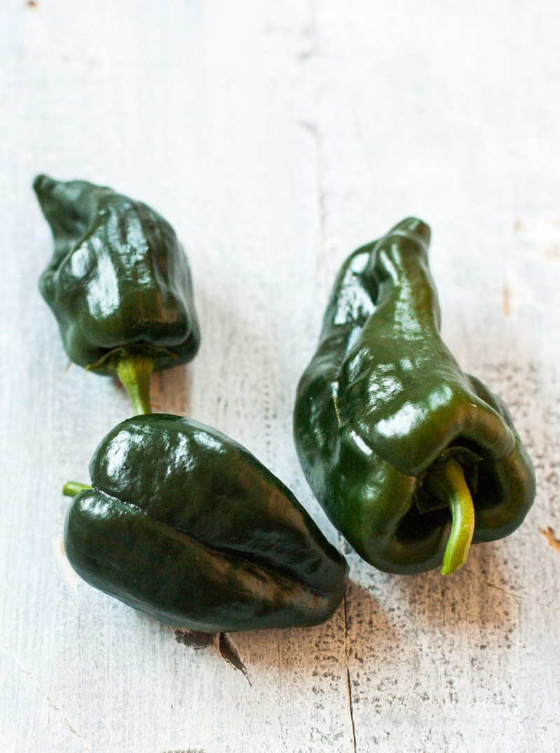 Three fresh poblano peppers on white wooden surface.