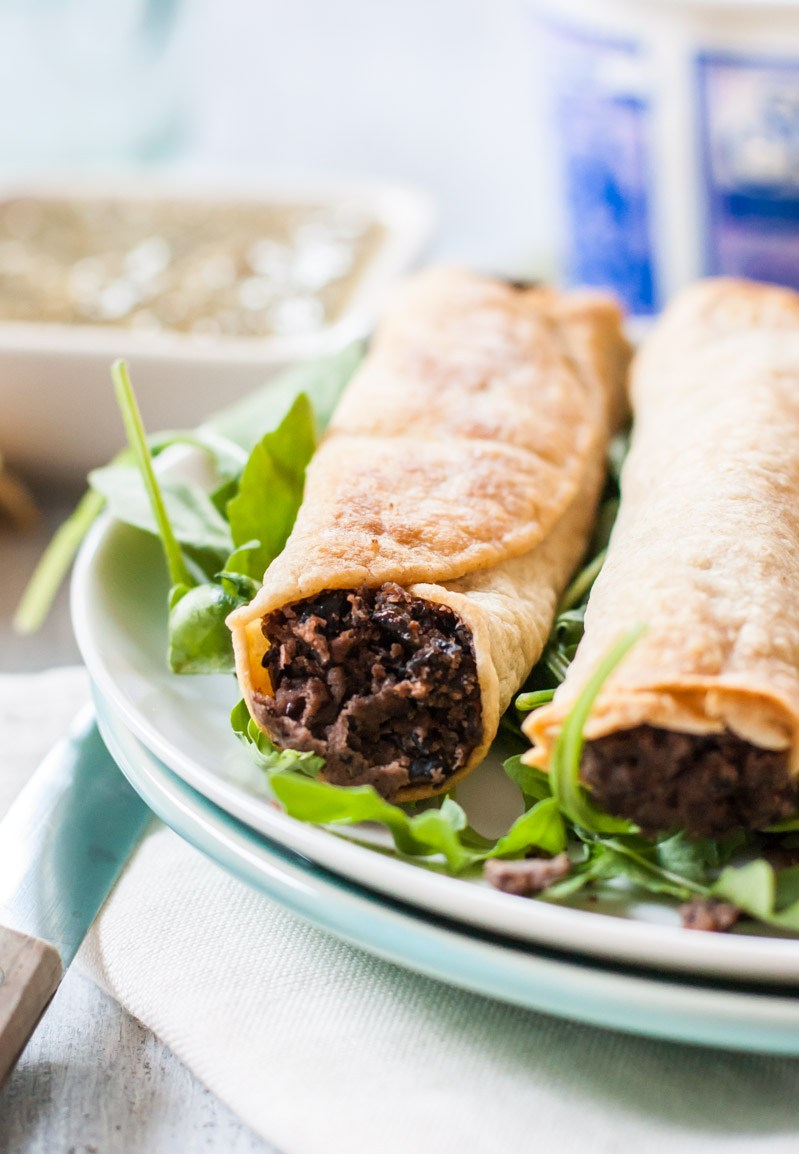 A close up of two slow cooker black bean and poblano pepper baked taquitos.