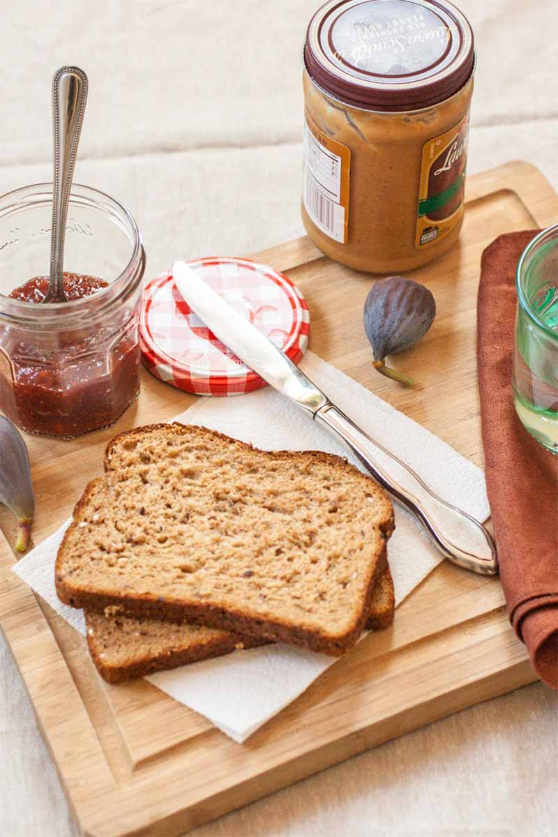 Vertical image of two pieces of whole wheat bread, a jar of fruit preserves with a spoon in it, with a knife next to it resting on the red and white patterned lid, a jar of peanut butter, two whole figs, and a reddish brown cloth with a green glass jar on top, on a wood cutting board.