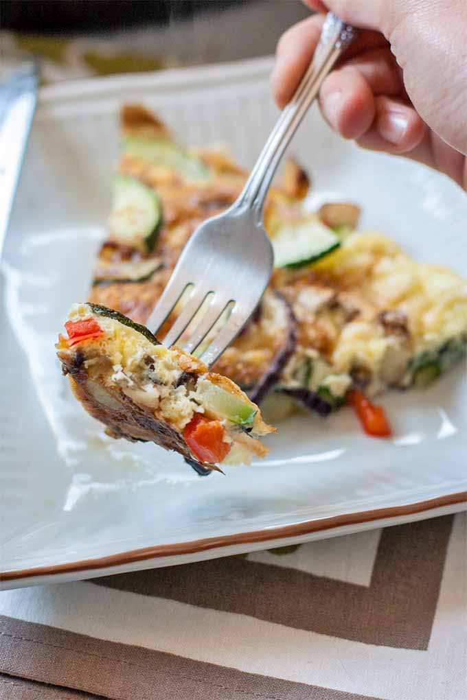A hand holds a forkful of potato, zucchini, red bell pepper, and onion frittata up to the camera, with a slice of the egg dish on a square white plate in the background, on top of a beige and white striped place mat.