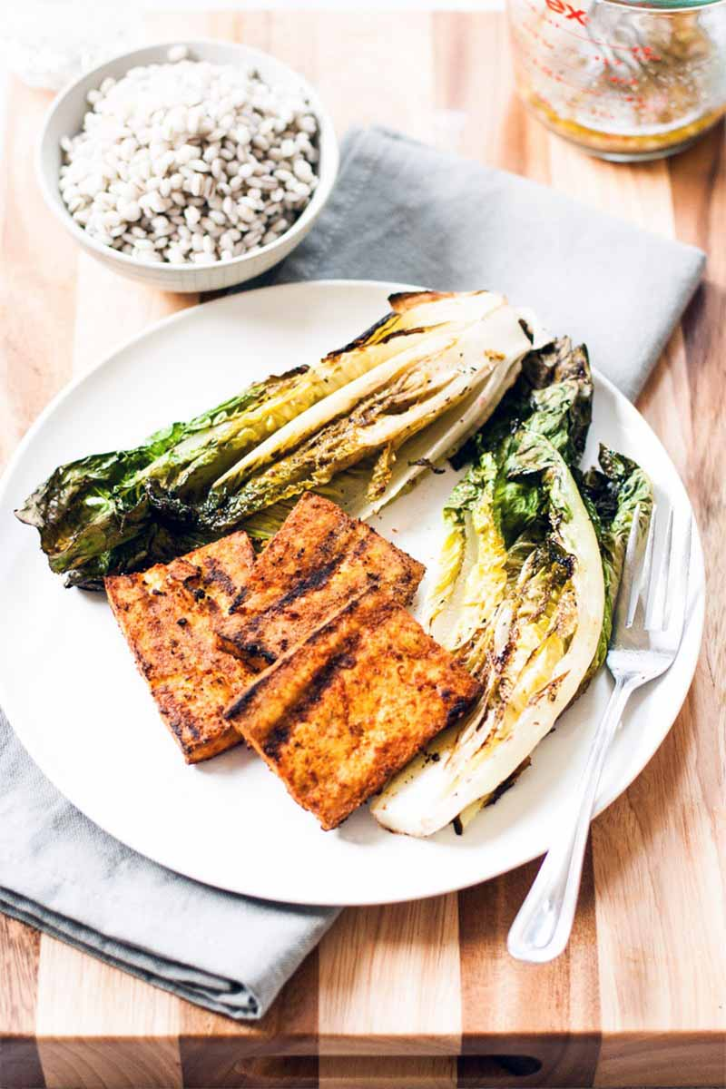 Two pieces of charred romaine lettuce and three pieces of grilled and marinated super firm soybean curd on a white pate with a fork, beside a small bowl of cooked barley, on a folded gray cloth on top of a wood cutting board.