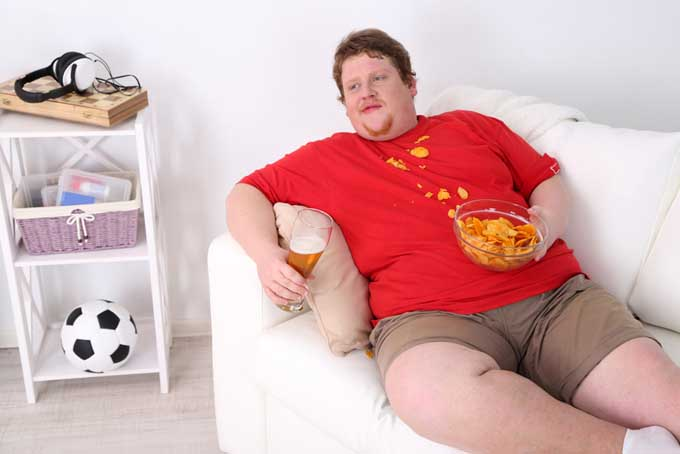 Unhealthy young man on couch with junk food | Foodal.com
