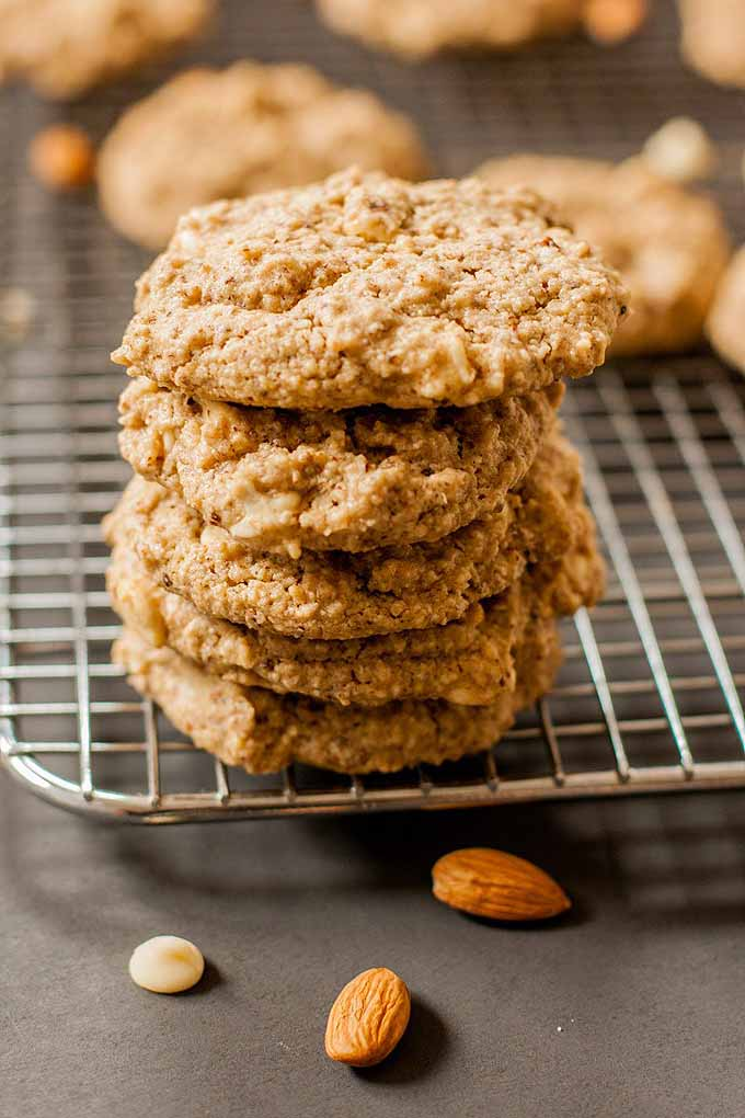 Closeup of a stack of six just-baked golden brown oat and almond cookies on a cooling rack.