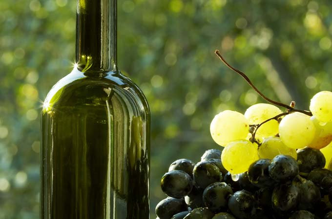 Homemade wine in green bottle with green and purple grapes to the right. Diffuesed wooded background.