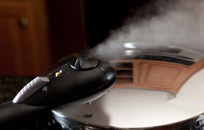steam escaping from top valve of pressure cooker