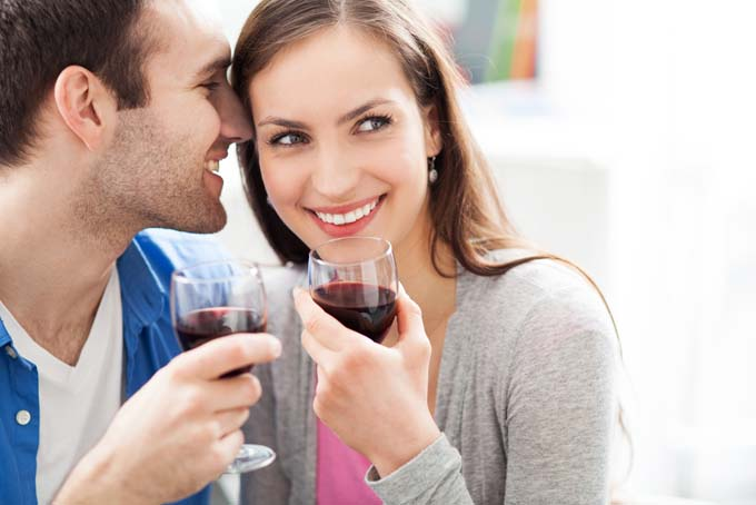 An attractive couple stand with wine glasses - the guy is wispering a secret into the woman's ear