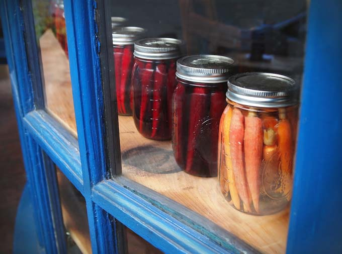 A row of carrots and parsnips pickled in mason jars is displayed in a glass window cabinet with blue frames.