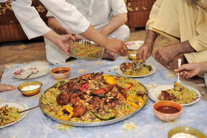 A group of Iraqi men dip food out of a platter of Kabsa