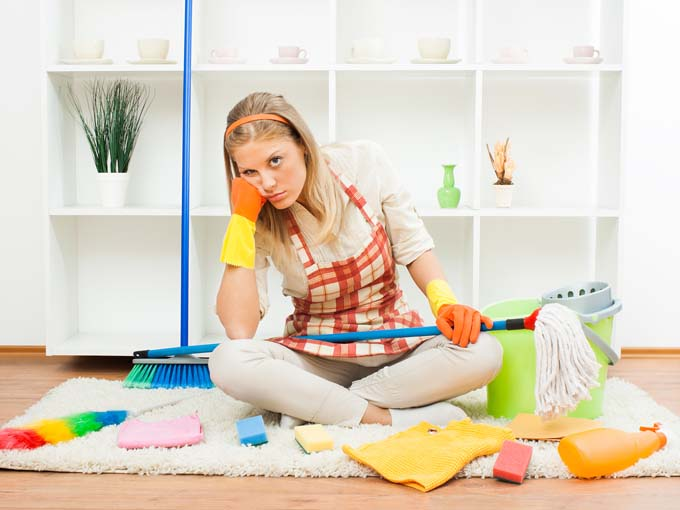 Attractive housewife sitting on kitchen floor looking frustrated with cleaning supplies around her.
