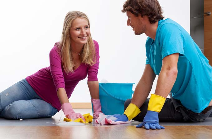 Man and Woman happily scurb the floor together