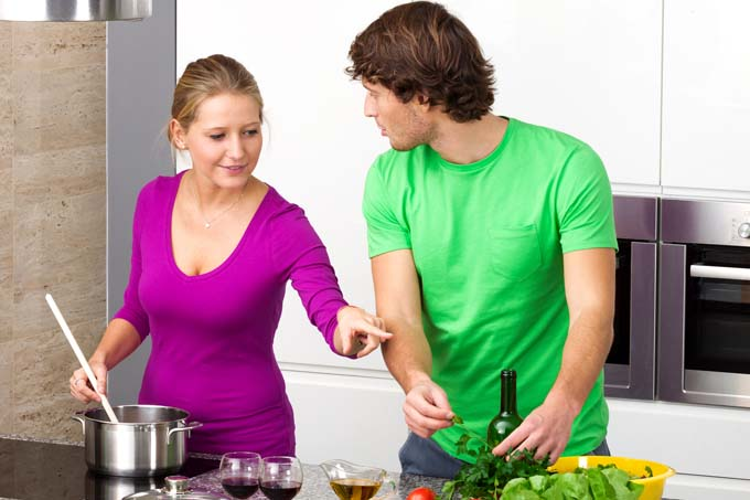 Man and woman cook food together