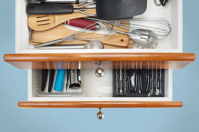 An organized kitchen drawer with utensils properly placed and clutter minimized.