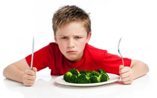 Grouchy young boy with plate of broccoli.