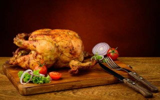 roasted chicken meat and vegetables on a wooden plate