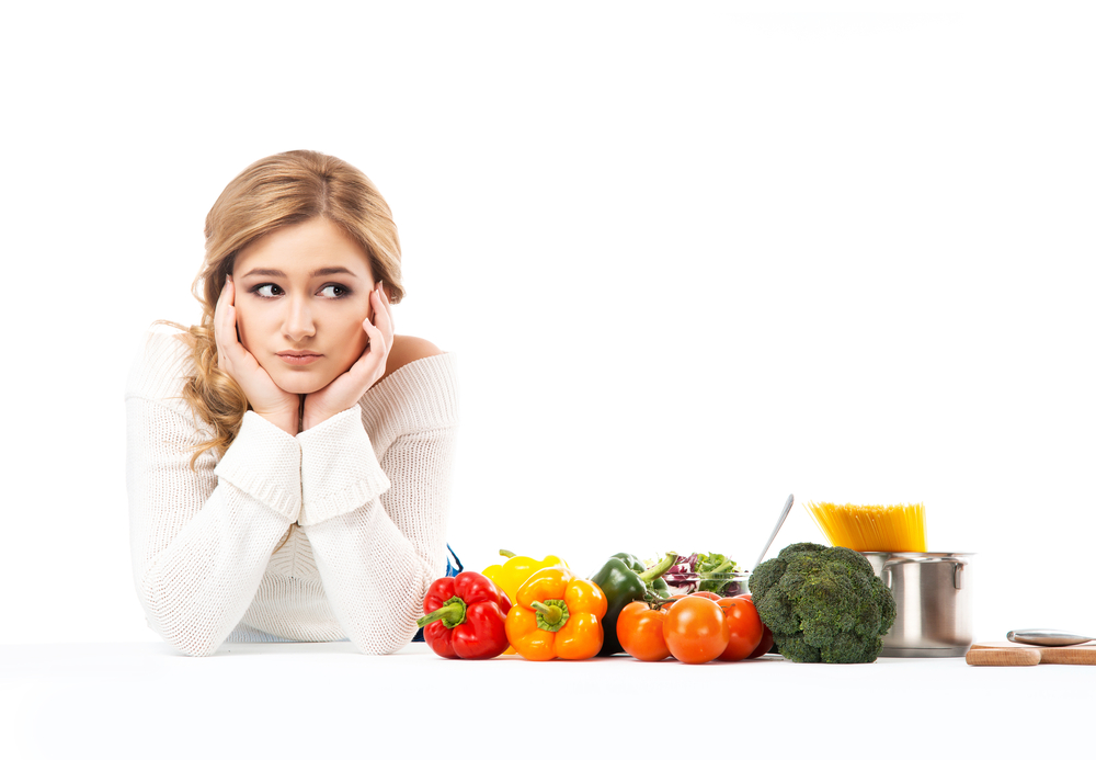 Yound blonde female confused on how to cook. She is wearing white shirt resting on her elbows on white table with colorful vegetables and cookware besides her. Isolated background.