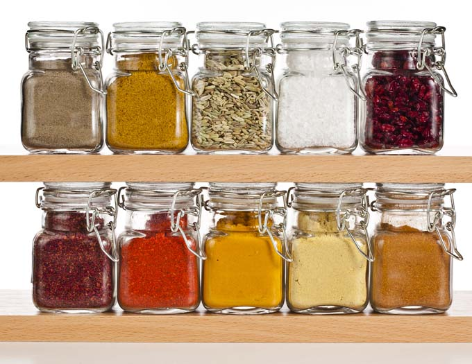 10 Large Jars of Spices sitting on two wood shelves with white background