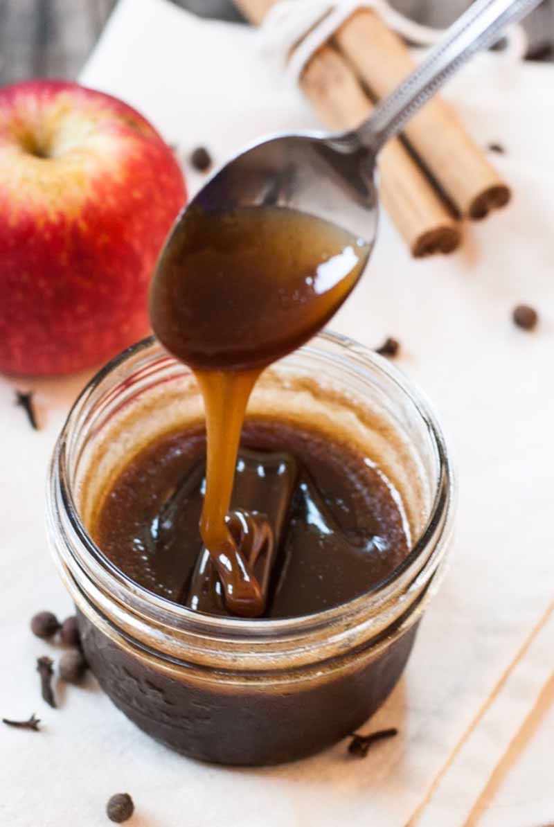 A spoon dipped into caramel sauce being dripped backed into a mason jar.