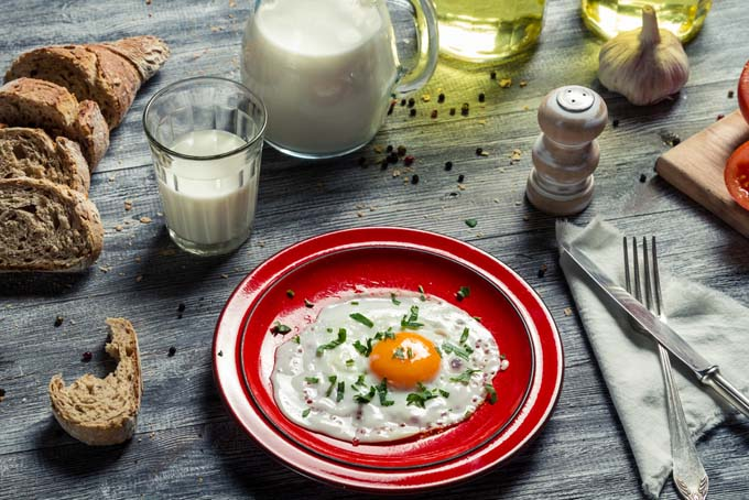 Fried egg on red plate on old wooden table; a pitcher of milk, glass of milk, and condements nearby