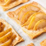 Oblique closeup shots of six rectangles of phyllo dough, topped with sliced spiced pears, baked on parchment paper.