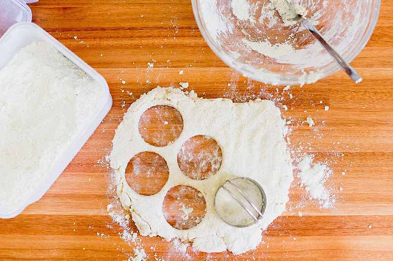 Overhead shot of a glass bowl coated with flour, rolled out dough with circles cut out, and a rectangular white plastic container of flour, on a brown wood surface.