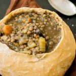 Horizontal close-up image of a vegetable and pulse stew in a bread bowl.