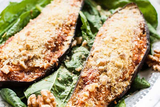 Close up of two halves of a marinara stuffed and roasted eggplant halves on a bed of leaf lettuce.