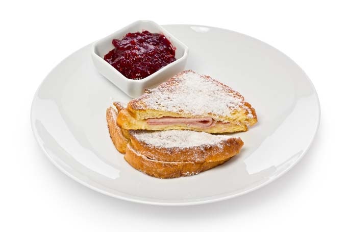 Monte Cristo sandwiche on white plat with rasberry jam in white rectangular cup- top view with isolated background