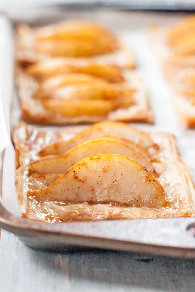 Closeup closely cropped oblique shot of pear phyllo tarts on a baking pan lined with parchment peper, with selective focus, on a white wood surface.