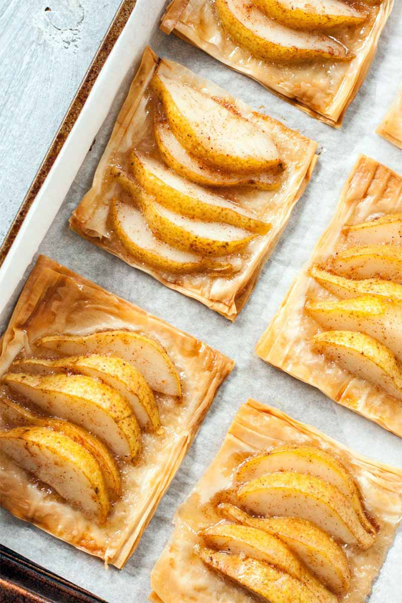 A paper-lined sheet pan of pear honey tarts, on a white wood surface.