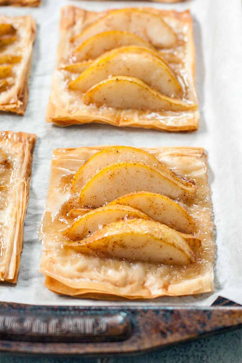 Four pear phyllo tarts on a well-used metal baking pan topped with a piece of white parchment paper.