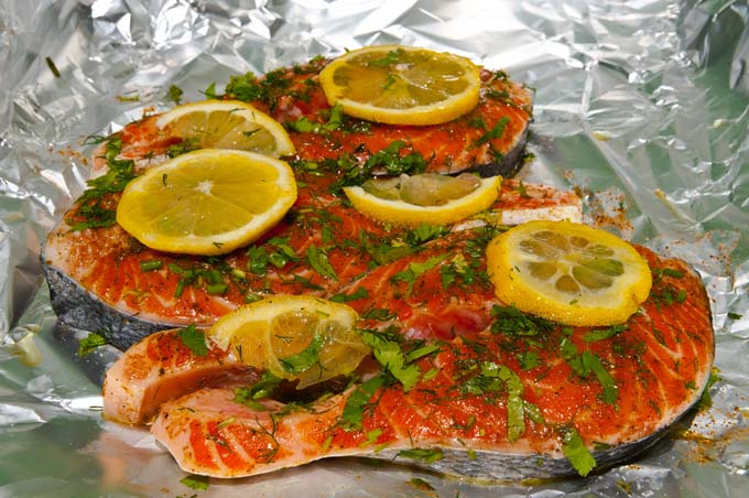 Salmon on an aluminum sheet with lemons and parsley