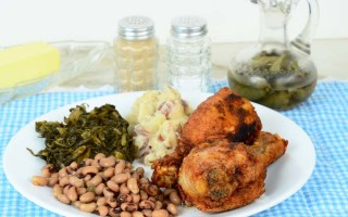 Southern fried chicks, turnip greens, black eed peas, fried potatoes and collard greens; on a blue and white checked table cloth; pepper, salt and sweet sourthen tea in background