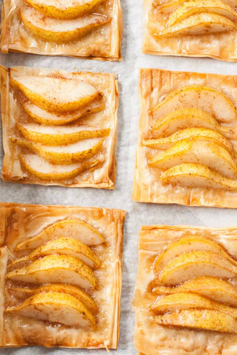 Top-down shot of six pear tarts on phyllo dough, on top of a sheet of parchment paper.