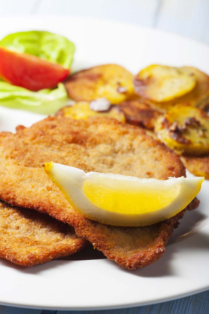 Wiener Schnitzel with Crispy Fried Potatoes Garnished with a Slice of Lemon | Foodal.com