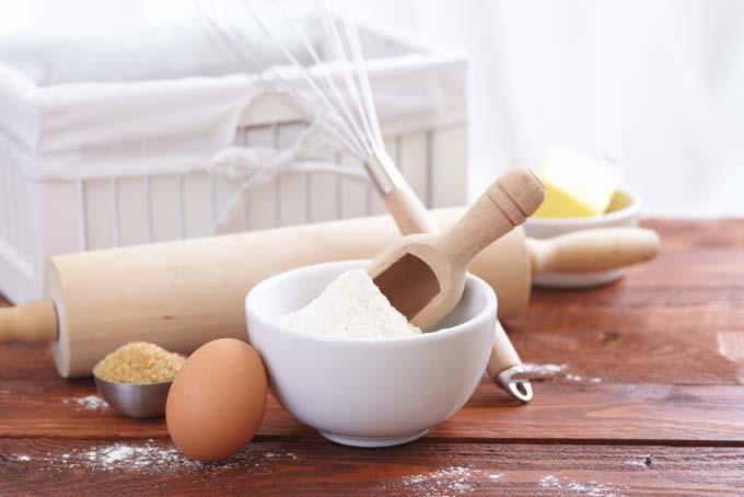 Baking tools such as rolling pin and ingrediants to incude flour, egg, and brown sugar spread on old wooden table
