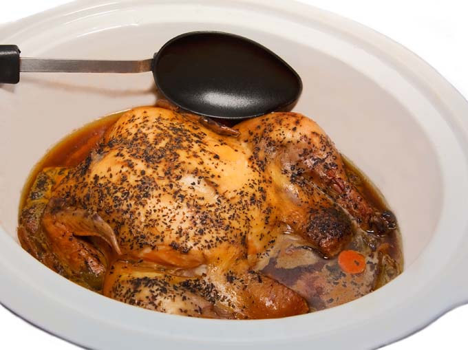 a whole cicken with herbs and spices slowly roasting in a crock pot