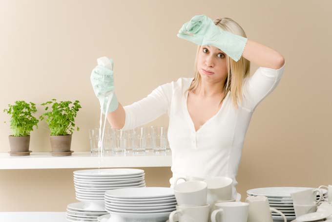 Blonde woman doing the dishes and sweating do the energy she is putting into burning calories